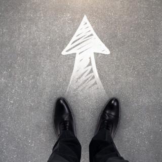 Мужские ноги в туфлях стоящие на стрелке нарисованной мелом на асфальте