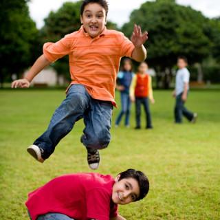 На зеленой полянке мальчики играют- один перепрыгивает через другого, который стоит на четвереньках.
